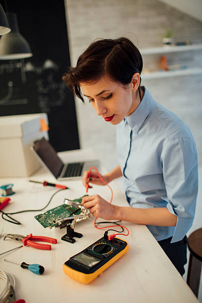 Young Woman Testing circuit board in her office. stock photo