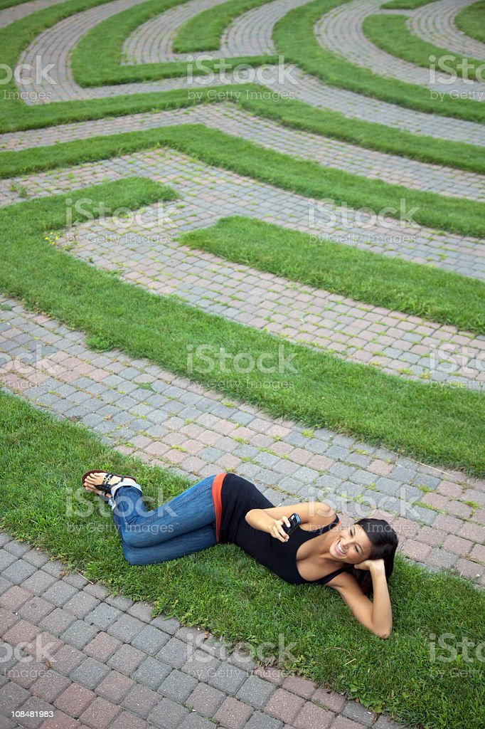 Young Woman Text Messaging in a Grass Maze royalty-free stock photo