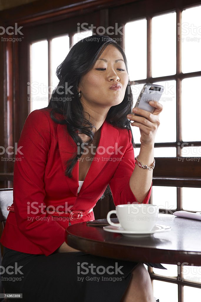 Young woman text messaging using mobile phone in restaurant royalty-free stock photo