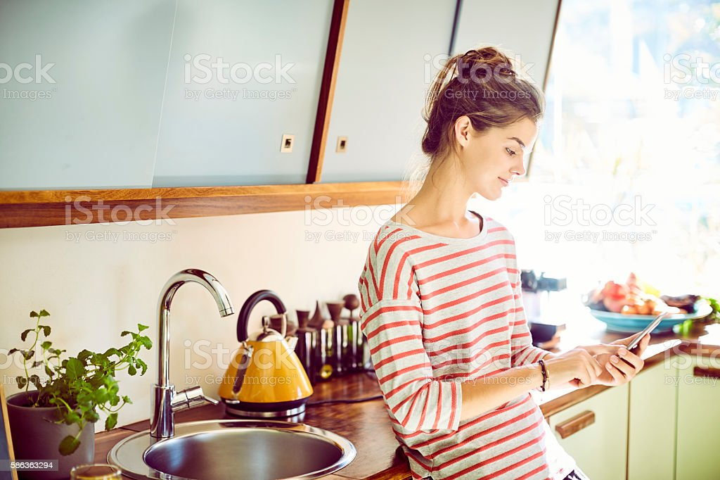 Young woman text messaging while leaning on kitchen counter stock photo