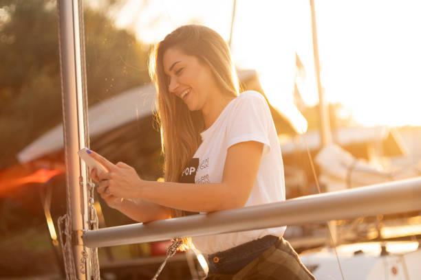 Junge Frau SMS und Segeln – Foto