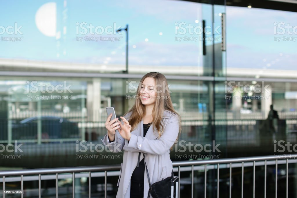 Young woman texting by smartphone near valise and airport zbiór zdjęć royalty-free