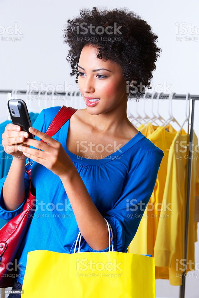 young woman texting carrying shopping bags royalty-free stock photo