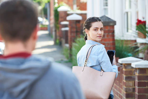 young woman texting for help on mobile phone whilst being stalked on city street - stalking stock photos and pictures