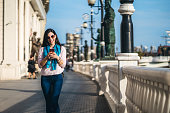 Young beautiful caucasian woman texting on her phone on the street in Skopje.