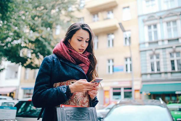 young woman texting in berlin - deutsche frauen stock-fotos und bilder
