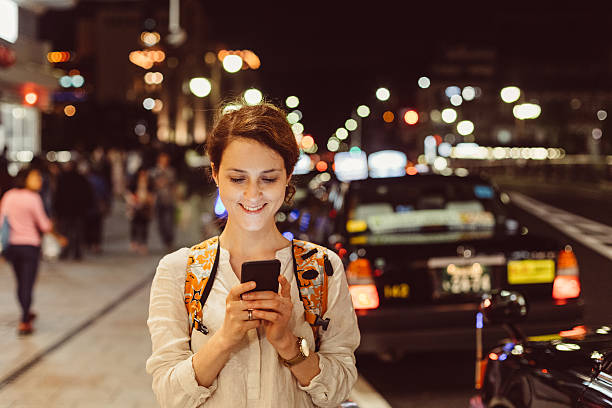 young woman texting in the city - rideshare stock photos and pictures