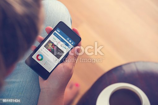 Woman holding Mobile phone with food diary app. The screen shows calories remaining with a heart shape cutting board with fresh vegetables. She is sitting relaxing drinking coffee
