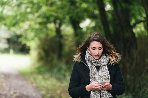 young woman texting on her mobile in a woodland setting.