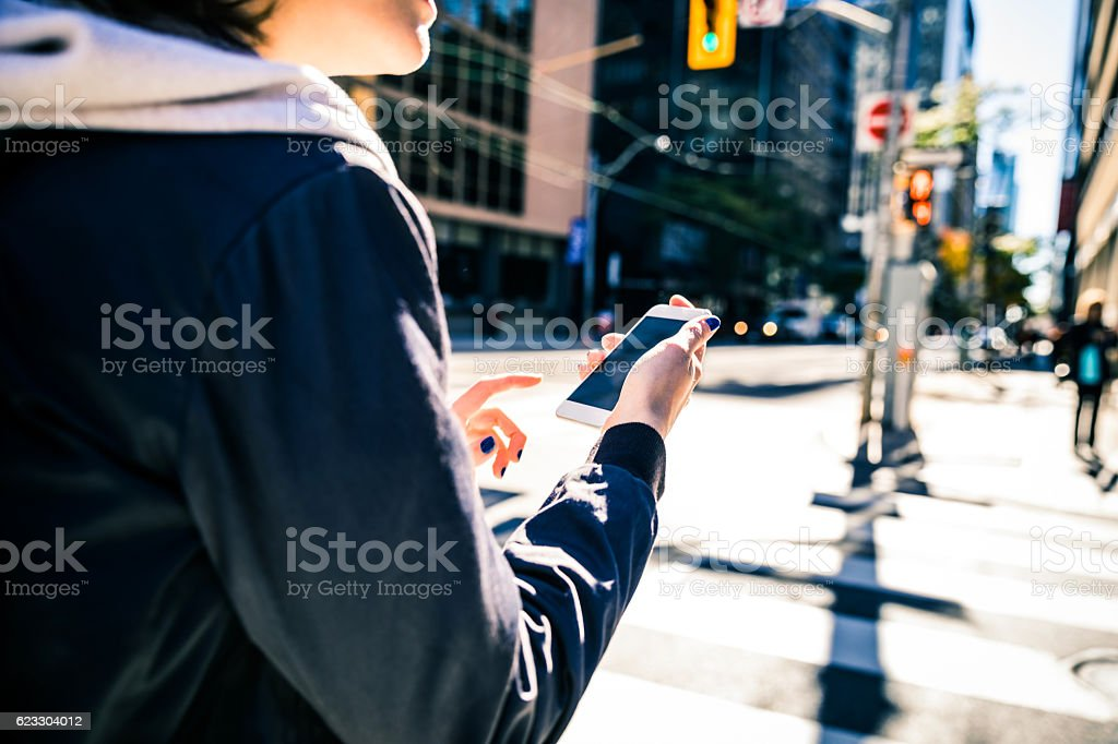 Young woman texting on mobile looking for car pool stock photo