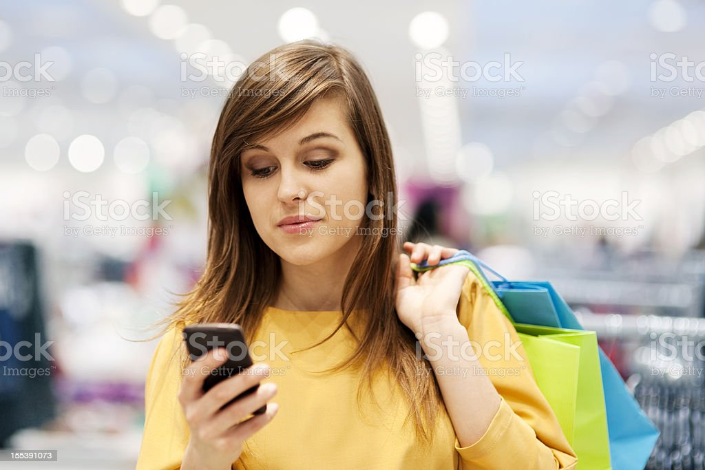 Young woman texting on mobile phone in store stock photo