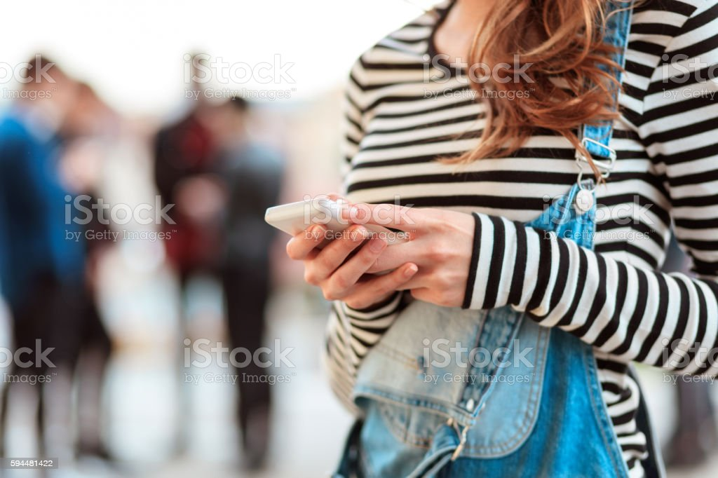 Young woman texting on smart phone outdoor Young woman texting on mobile outdoor. Defocused group of people in the background. 20-29 Years Stock Photo