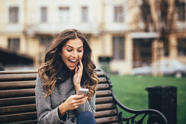 Young woman texting on smart phone outdoors stock photo