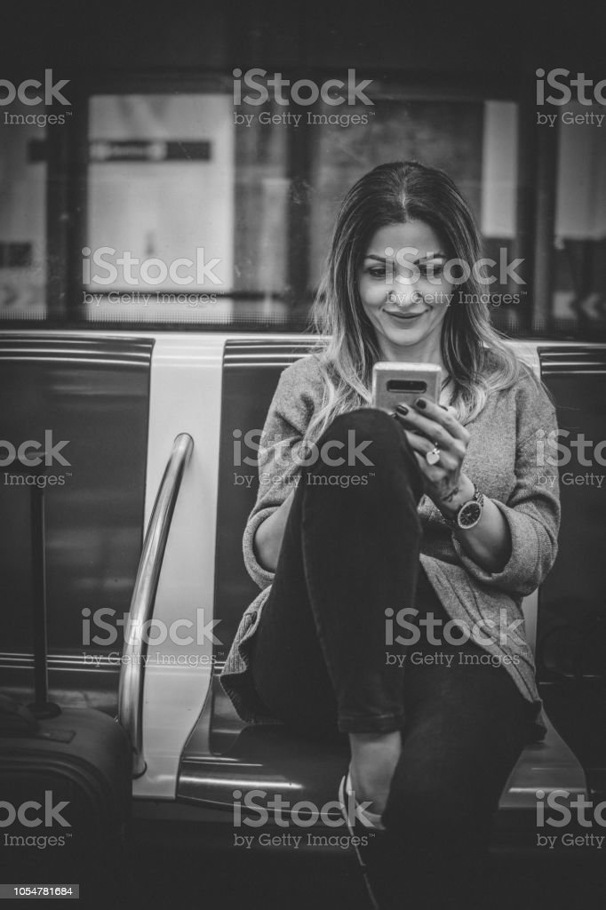 Young woman texting while commuting stock photo
