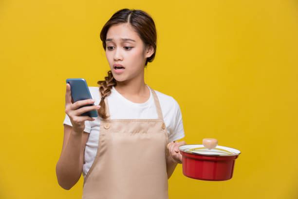 young woman texting while cooking - fail cooking imagens e fotografias de stock