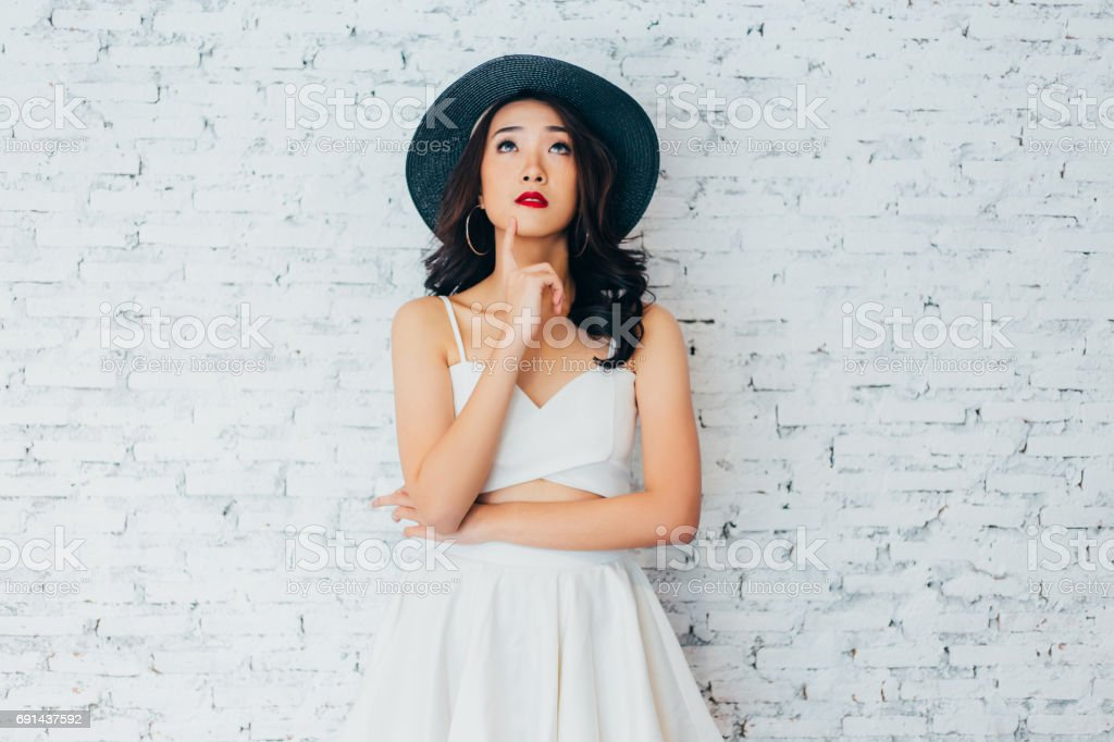 Young woman thinking about something with fashionable summer hat over white wall background with copy space stock photo