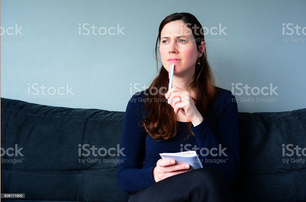 Young woman thinking about to do list at home stock photo
