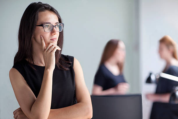 Young woman thinking in business office - foto de acervo