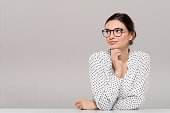 Beautiful young businesswoman wearing glasses and thinking with hand on chin. Smiling pensive woman with eyeglasses looking away isolated on grey background. Fashion and contemplative girl smiling and meditating on project.
