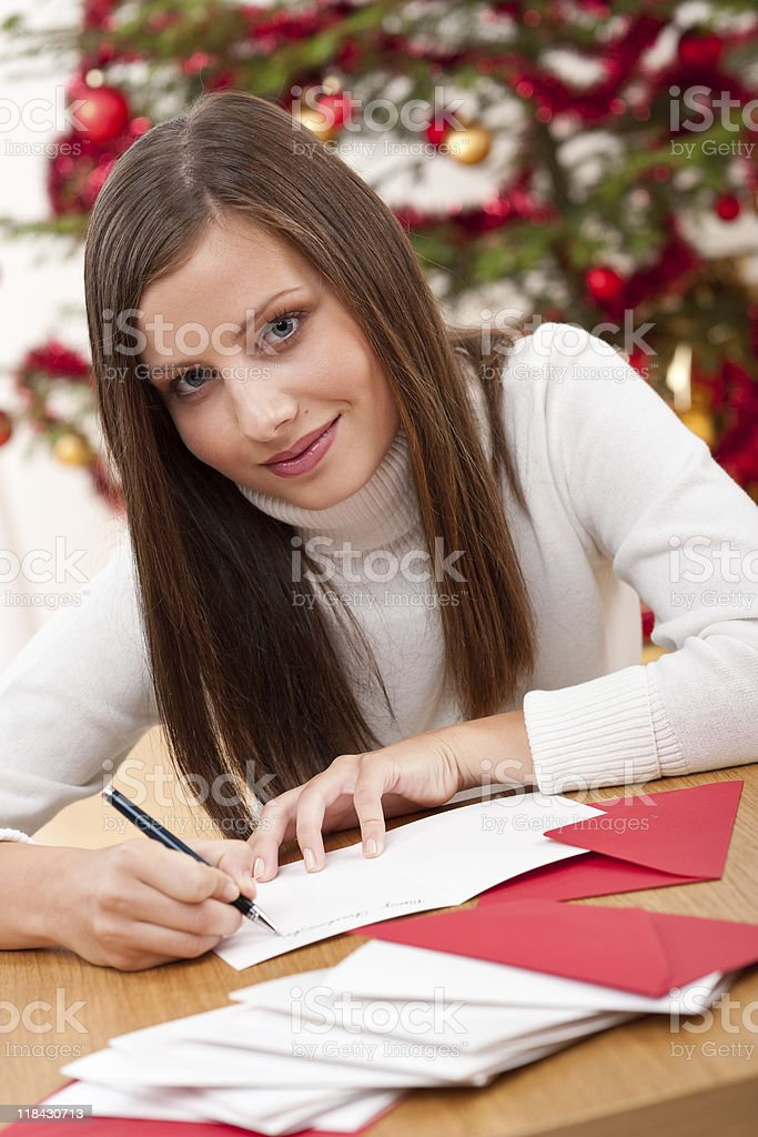 Young woman thinking while writing Christmas card royalty-free stock photo