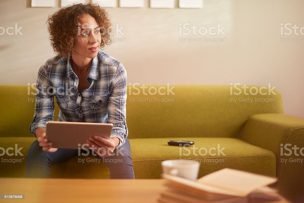 young woman thinking with her tablet stock photo