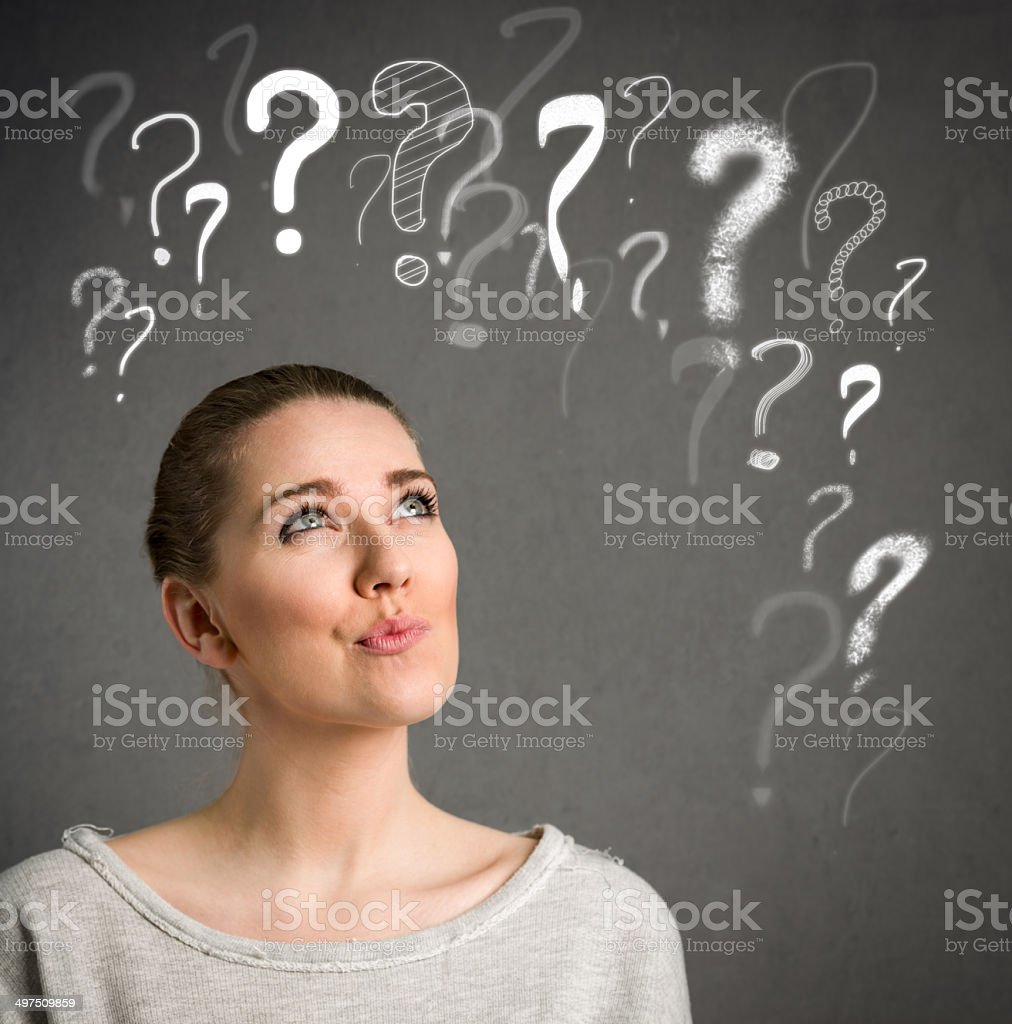 Young woman thinking with question marks over head stock photo