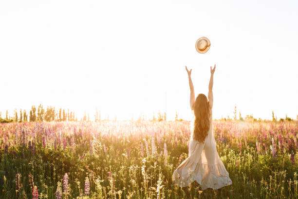 Young woman throw up straw hat in flower field on sunset. Freedom concept, horizontal shot stock photo