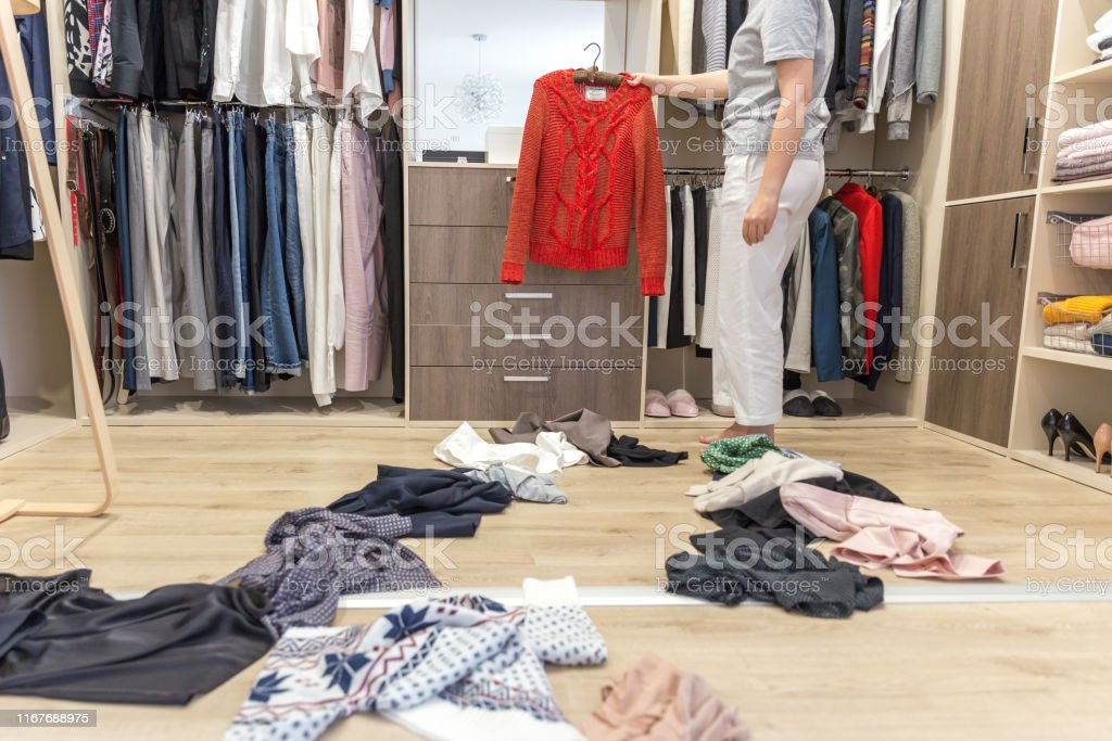 Young woman throwing clothes in walk in closet. Mess in wardrobe and...