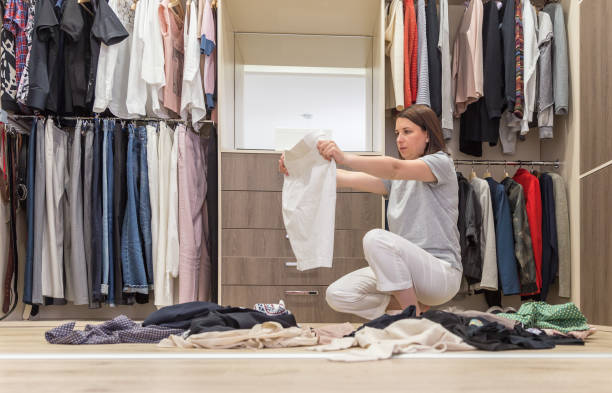 Young woman throwing clothes in walk in closet. Mess in wardrobe and dressing room Young woman throwing clothes in walk in closet. Mess in wardrobe and dressing room concept arrangement stock pictures, royalty-free photos & images