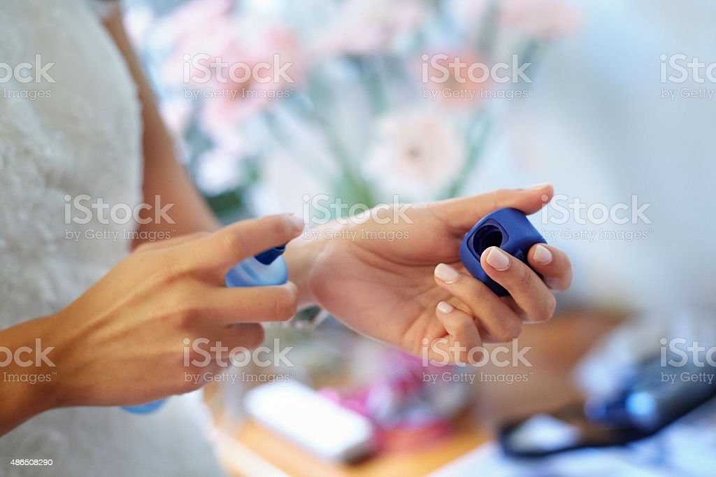 Mujer joven echándose colonia en la muñeca - foto de stock