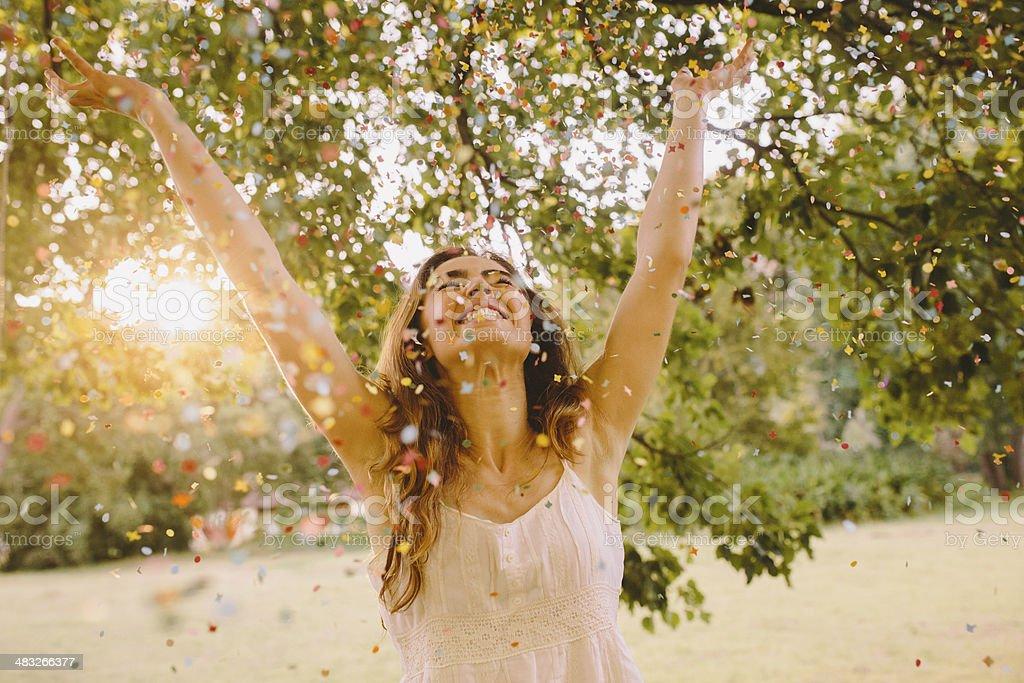 Jovem mulher jogando Confete no parque - foto de acervo
