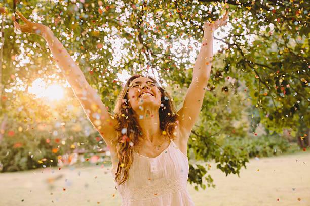 若い女性が公園で紙吹雪を投げる ストックフォト