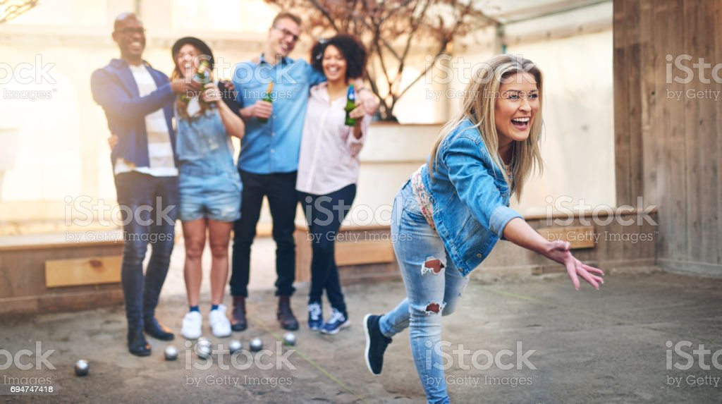Young woman throwing petanque ball playing with friends stock photo