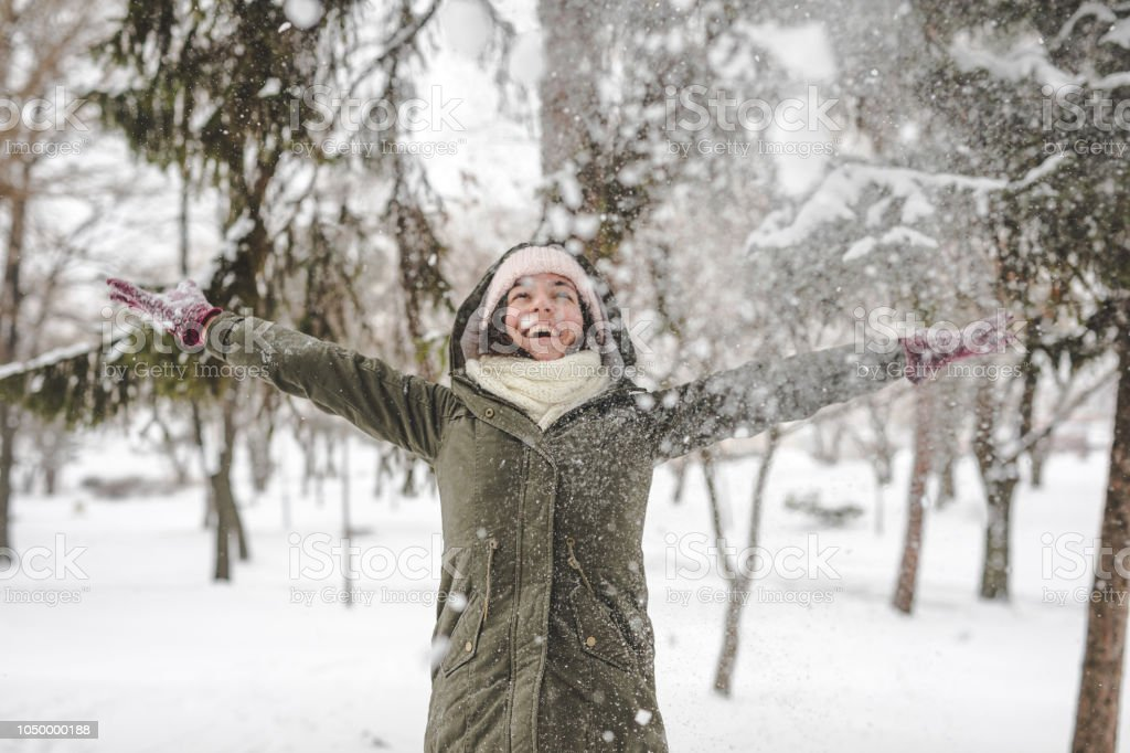 Young woman throwing snow stock photo