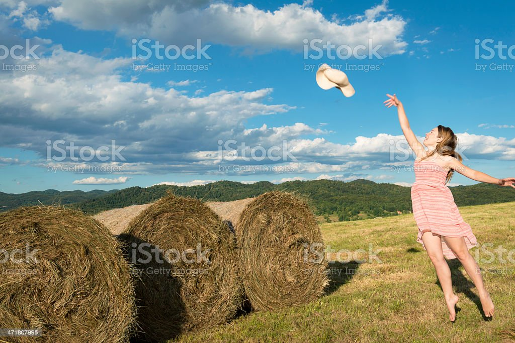 Young Woman Throwing Straw Hat Over Bale Silage Alps royalty-free stock photo