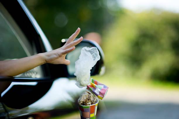 Una joven tira los desechos del coche - una taza de café y una bolsa. Contaminación ambiental, enfoque selectivo, luz de fondo - foto de stock