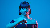 istock Young woman thumb down gesture isolated on blue neon copyspace 1303517464