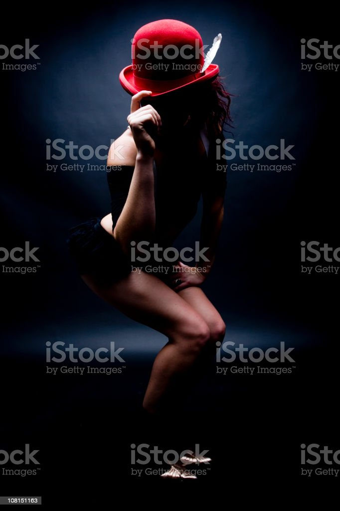 Young Woman Tipping Red Bowler Hat, Low Key stock photo