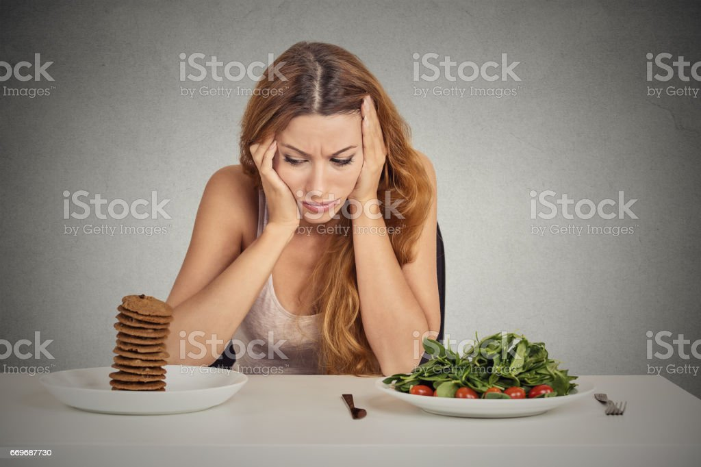 Young woman tired of diet restrictions deciding whether to eat healthy food or sweet cookies stock photo