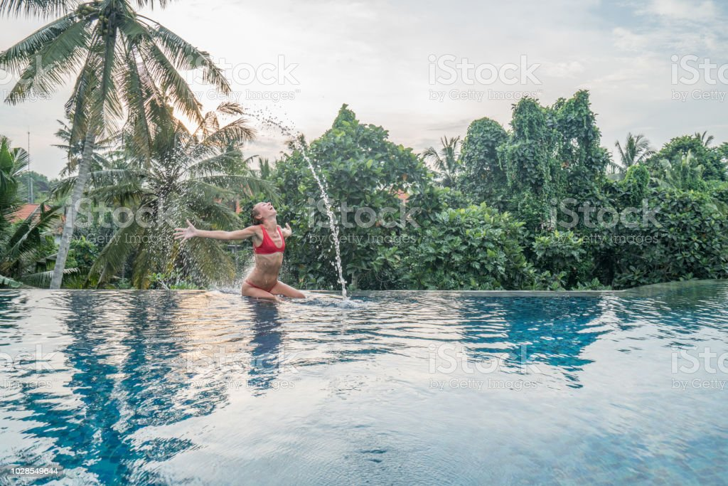 Young Woman Tossing Hair In Water At Infinity Swimming Pool Bali Indonesia People Ravel Fun Vacations Resort Concept Stock Photo Download Image Now
