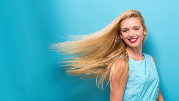 mujer joven sacudiendo su cabello - sólido fotografías e imágenes de stock