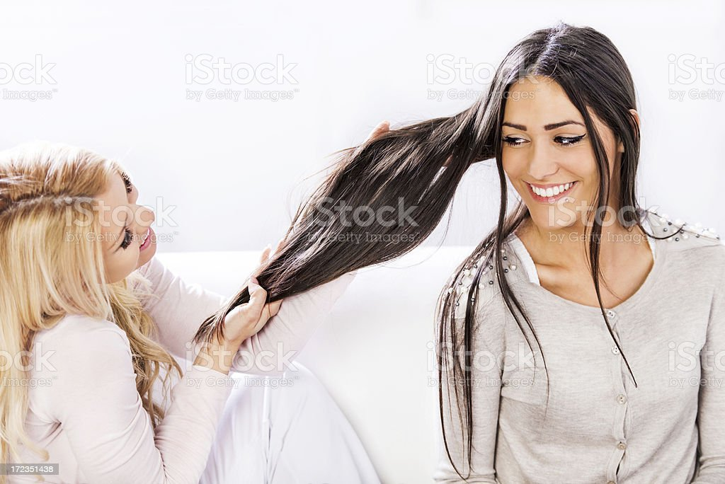Young woman touching her friend's long hair royalty-free stock photo
