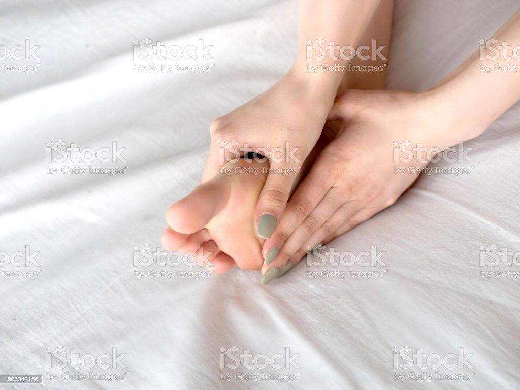 Young woman touching her leg on bed zbiór zdjęć royalty-free
