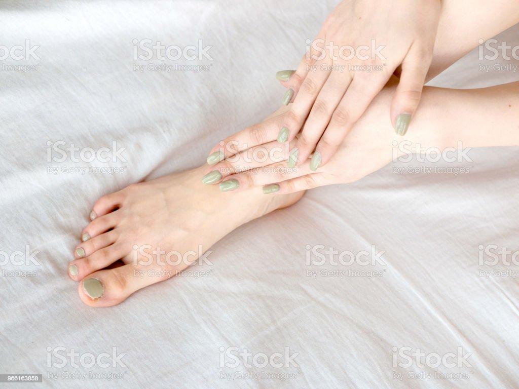 Ung kvinna röra hennes ben på sängen - Royaltyfri Ben Bildbanksbilder