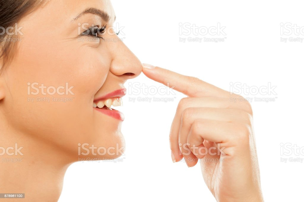 Young woman touching her nose with her finger stock photo