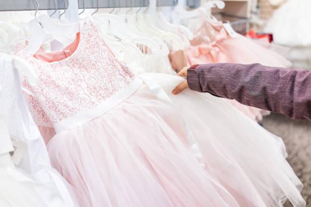 junge frau berühren einer hochzeit blumenmädchen partykleid in boutique-discounter, rosa kleider hängen rack kleiderbügel zeile closeup mit weißer spitze, tüll, design - tüllkleid stock-fotos und bilder
