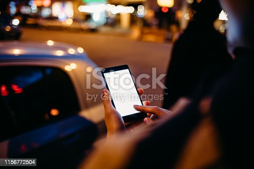 istock Young woman touching smart phone standing 1156772504