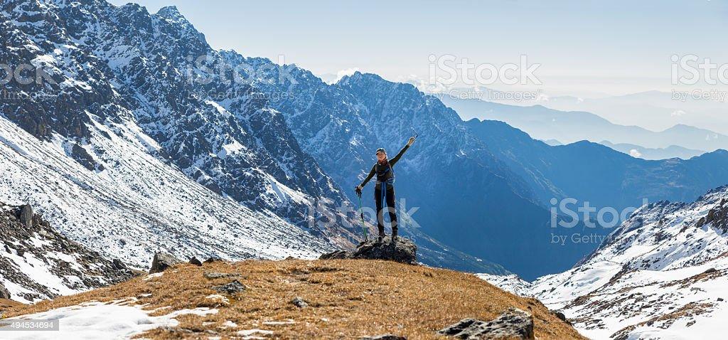 Young woman tourist backpacker standing mountain edge panorama. stock photo