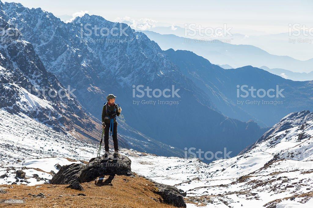 Young woman tourist backpacker standing rock mountain edge. stock photo