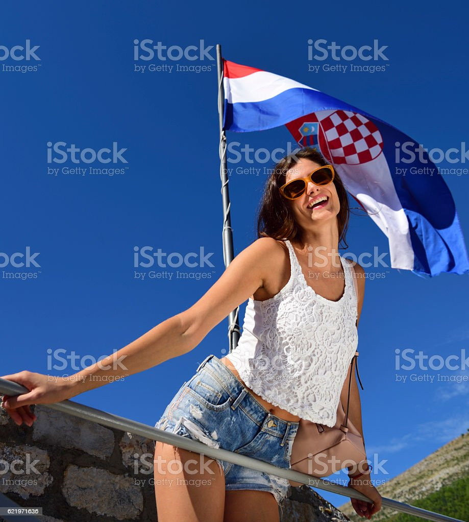 Young woman tourist Dubrovnik, wall, and flag in background stock photo